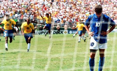 Baggio se lamenta após a perda do pênalti e os brasileiros comemoram o tetra ao fundo